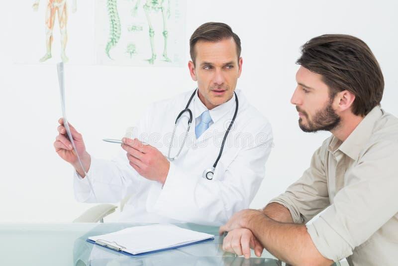 解释脊椎X-射线的男性医生对患者 图库摄影