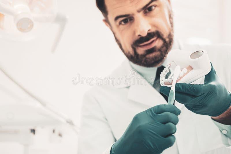 解释规则正确刷牙的牙医 免版税库存图片