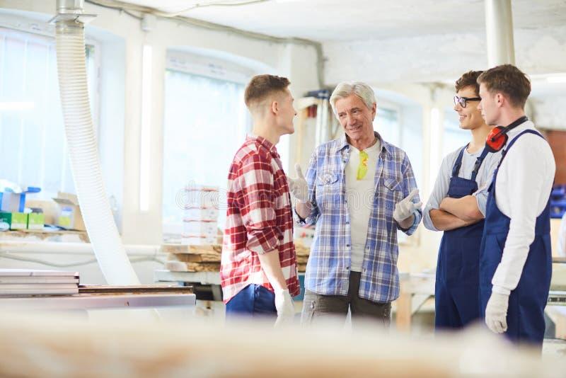 解释规则的熟练的木匠对年轻实习生在车间 免版税图库摄影
