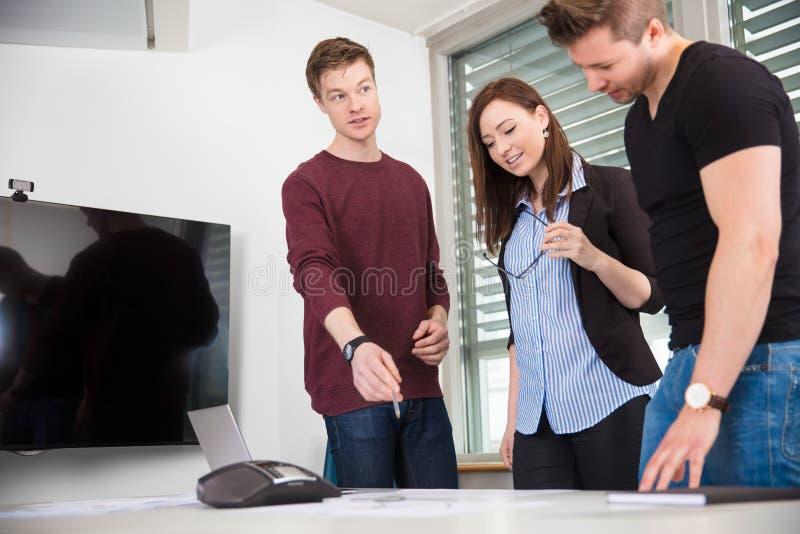 解释计划的商人对工友在书桌 免版税库存照片