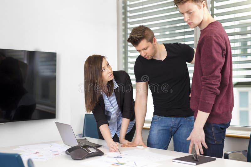 解释计划的女实业家对工友在书桌 免版税库存照片