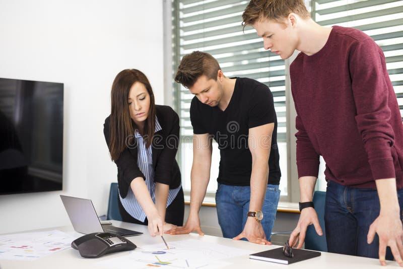 解释计划的女实业家对男性同事在书桌 免版税库存图片