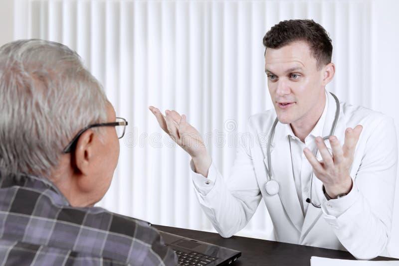 解释诊断的医生对他的年长患者 库存照片