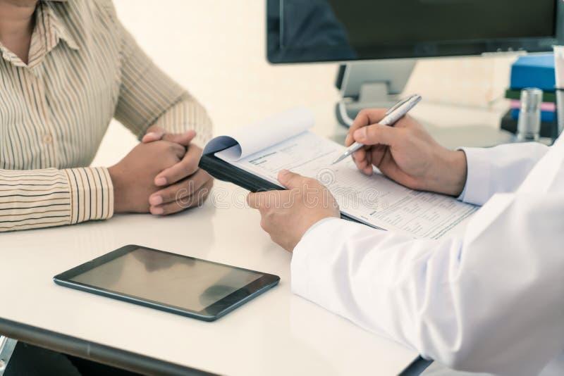 解释诊断的男性医生对患者 妇女患者看担心,当听的床新闻 免版税库存照片