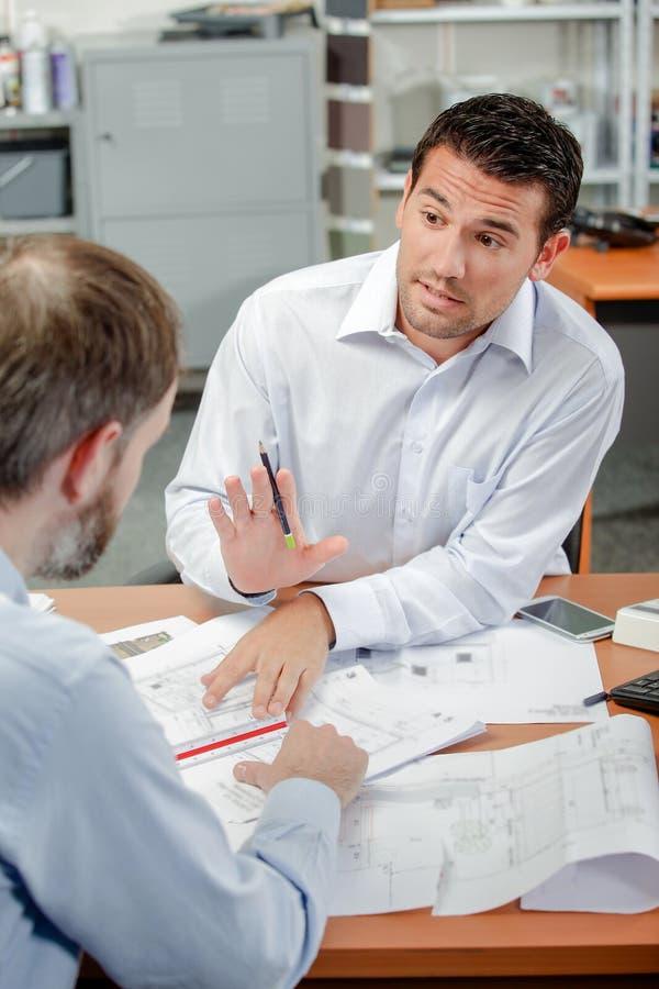 解释费用的建筑师对客户 免版税图库摄影