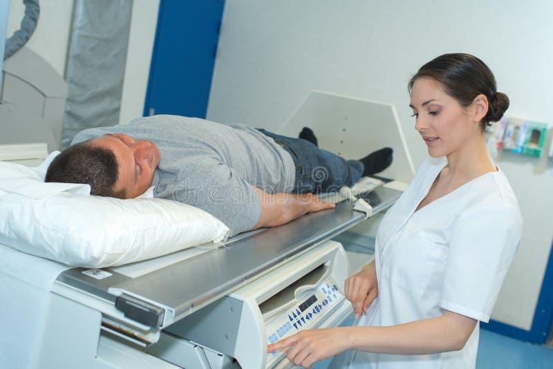 解释X-射线的技术员对患者 库存照片