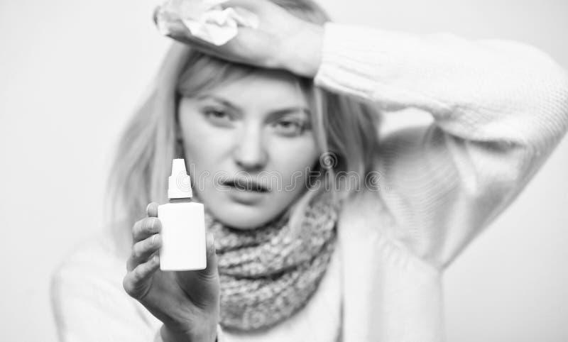 解除过敏症状 有鼻涕的不健康的女孩使用鼻孔喷射 病的妇女喷洒的疗程到鼻子里 免版税库存照片