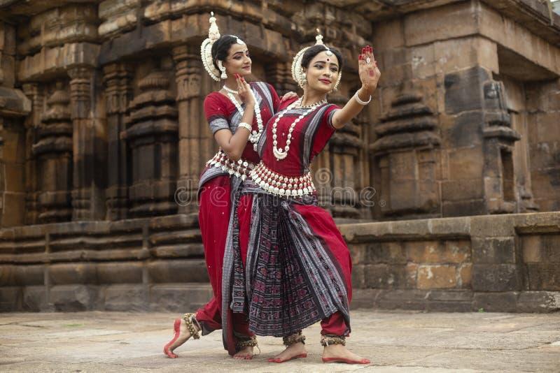 触击在Mukteshvara寺庙,布巴内斯瓦尔,Odisha,印度前面的两位印度古典odissi舞蹈家一个姿势 免版税库存照片