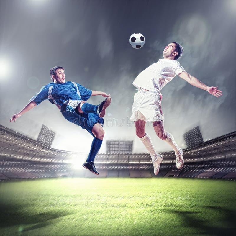 触击球的二位足球运动员 免版税库存图片