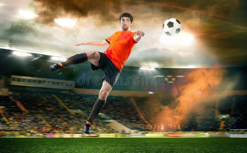 触击球的足球运动员在体育场 库存照片