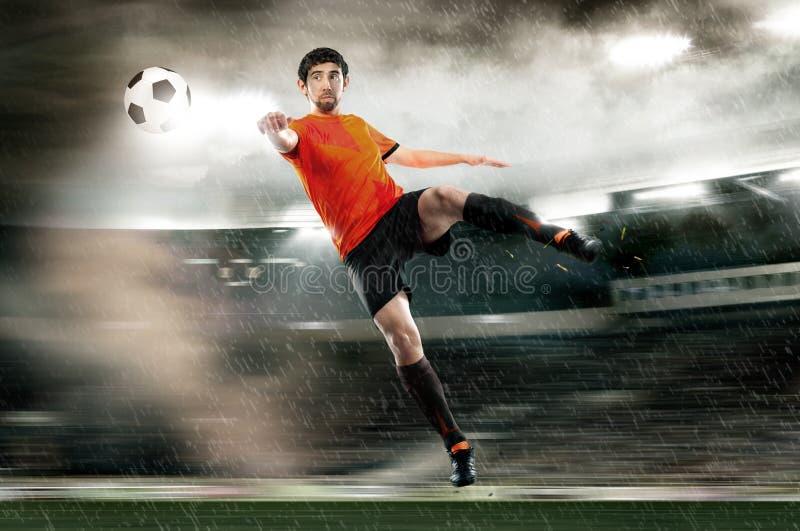 触击球的足球运动员在体育场 免版税库存图片