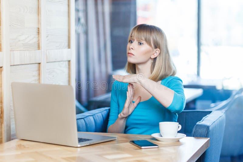警告有金发的可爱的少女自由职业者画象在蓝色女衬衫在咖啡馆坐并且打视频通话  库存图片
