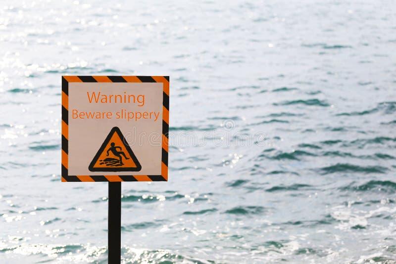 警告警告标记当心溜滑在海边区域 免版税图库摄影