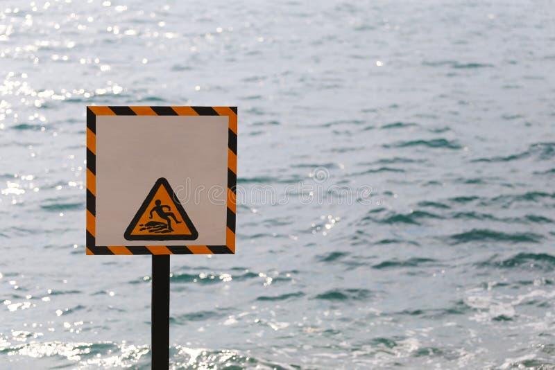 警告警告标记当心溜滑在海边区域 库存图片