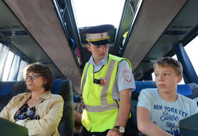 警察路警察巡逻的审查员检查城市间的乘客公共汽车的内部 免版税图库摄影