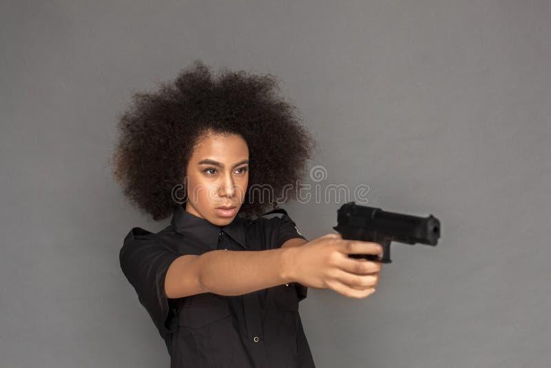 警察 混血儿在灰色瞄准的枪隔绝的妇女身分被集中 免版税库存照片