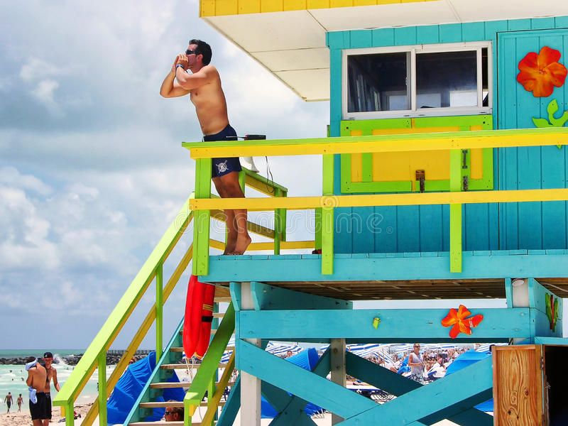 从警报的救生员到海滩的人民 免版税库存图片