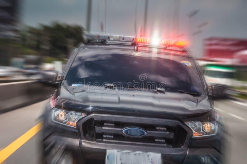 警车迅速迅速移动打开警报器,驾驶沿t 免版税库存照片