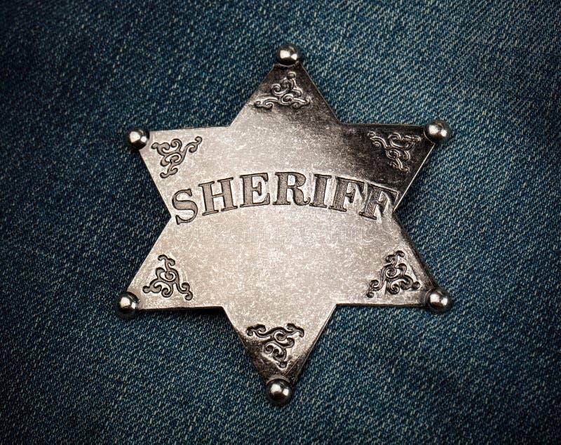 警长在蓝色牛仔布背景的星徽章 免版税库存图片
