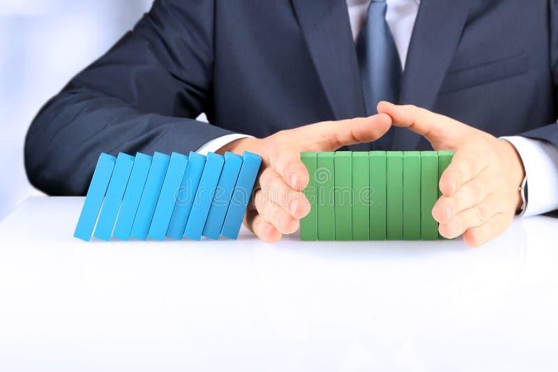计划、风险和战略在事务,拿着木块的商人 停止多米诺的作用商人 库存照片