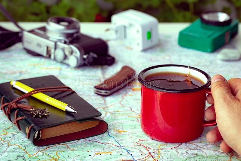 计划与一张地图的一次旅行在一杯茶和野营的设备旁边 库存图片