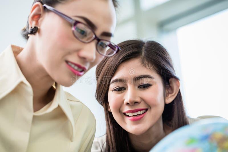 计划世界优势的女实业家在他们的办公室 免版税库存图片