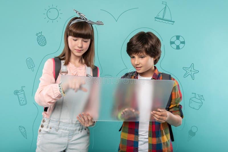 计划他们的旅途的现代孩子,当看透明屏幕时 免版税库存图片