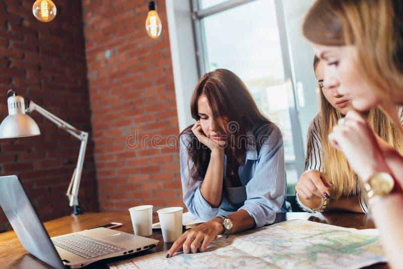 计划假期的女性办公室工作者使用地图 库存照片