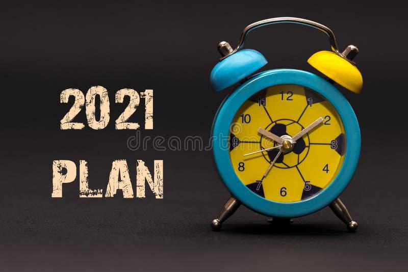 2021计划写与闹钟在黑纸背景 图库摄影