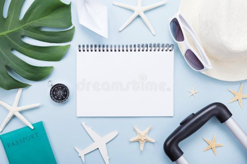 计划暑假、假期和旅行 有旅游业辅助部件的旅客笔记本在蓝色台式视图 平的位置 库存图片