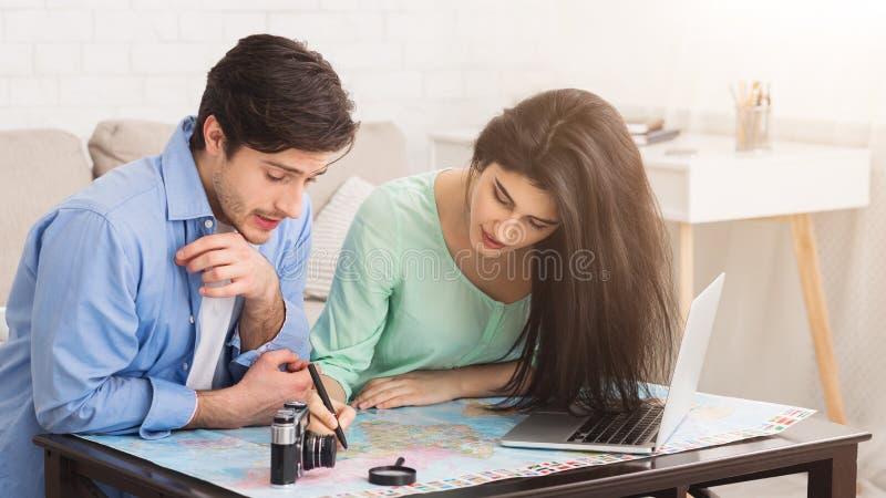 计划的游览一起 在家学习地图的夫妇 免版税图库摄影