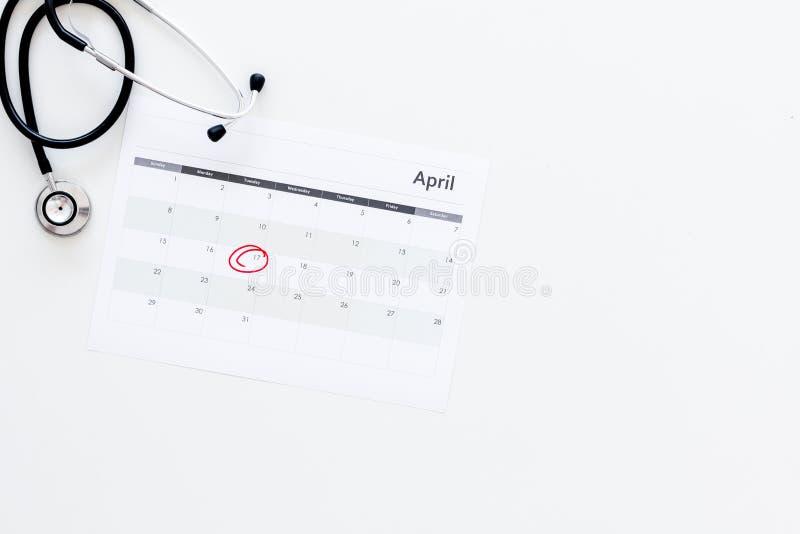 计划的身体检查概念 规则身体检查 在白色的日历与盘旋的日期和听诊器 免版税图库摄影