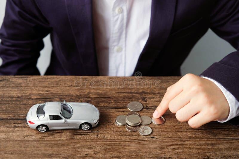 计数与小汽车模型的商人的手硬币在木 免版税图库摄影