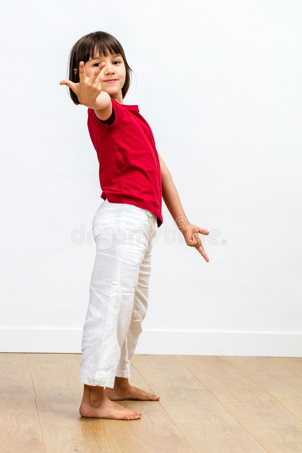 计数与手指和轻松的肢体语言的微笑的骄傲的孩子 库存图片