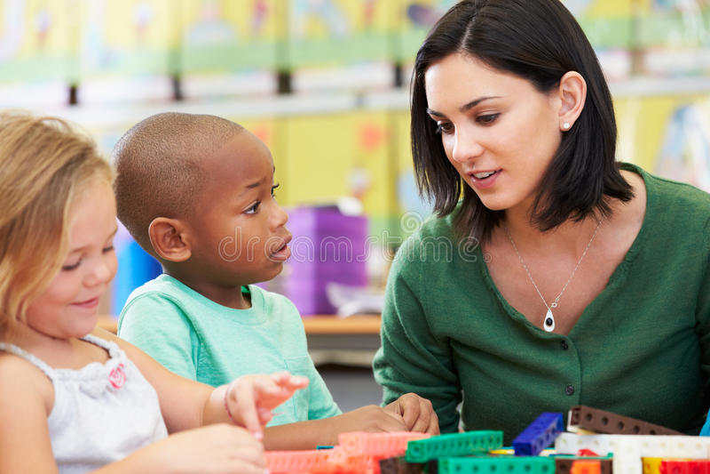 计数与老师的基本的学生在教室 免版税库存图片