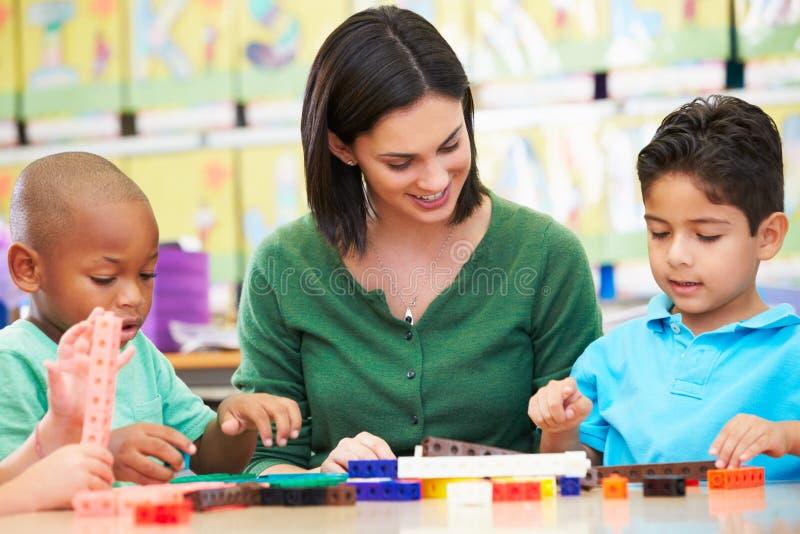 计数与老师的基本的学生在教室 免版税图库摄影