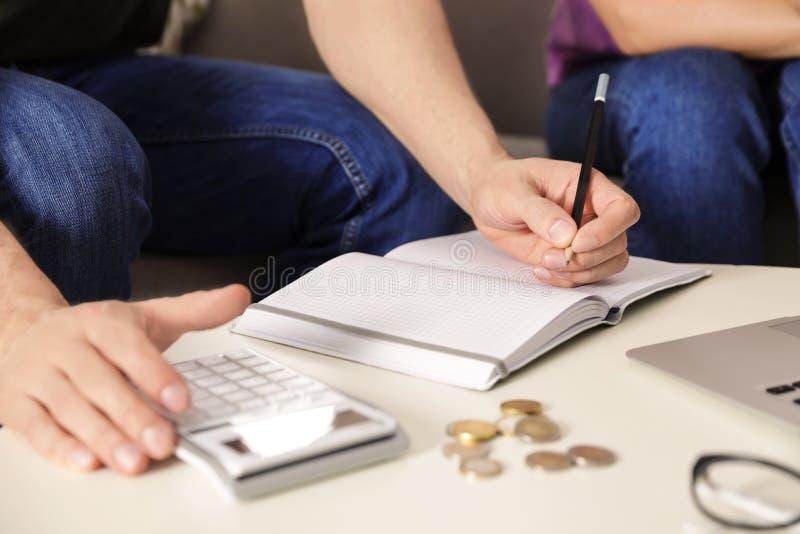 计数与计算器的人金钱在桌上 免版税库存照片