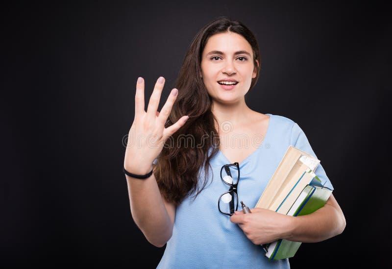 计数四的年轻美丽的学生妇女 免版税图库摄影