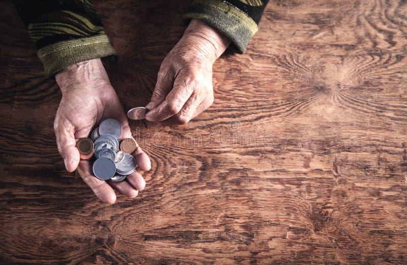 计数在木桌上的年长妇女金钱 图库摄影