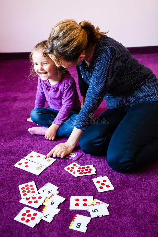 计数她的小女儿的母亲教学 免版税图库摄影