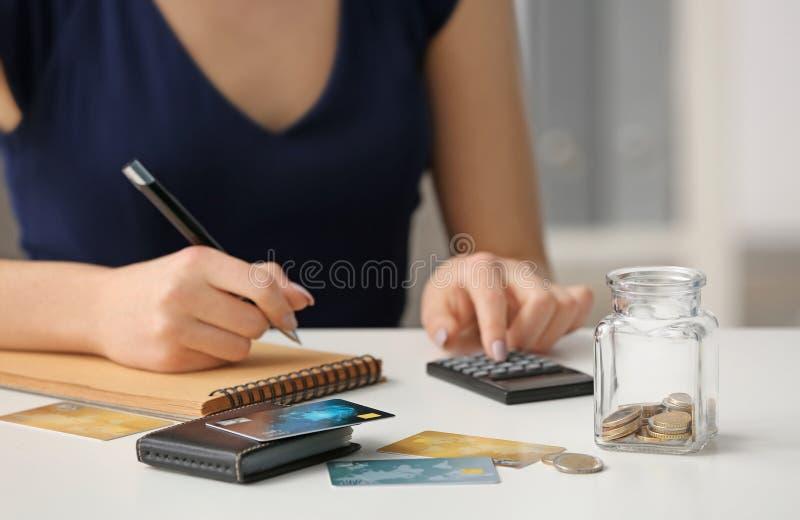 计数收入的妇女在桌上 储款概念 免版税库存图片