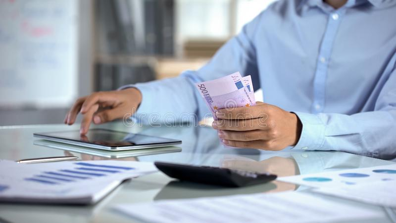 计数欧元和计划公司预算的商人由片剂应用 图库摄影