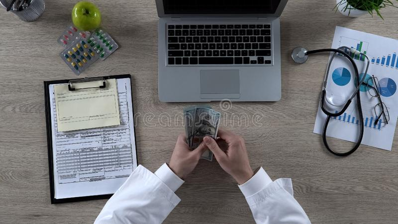 计数许多美金,昂贵的医疗保健的医护人员顶视图 免版税图库摄影