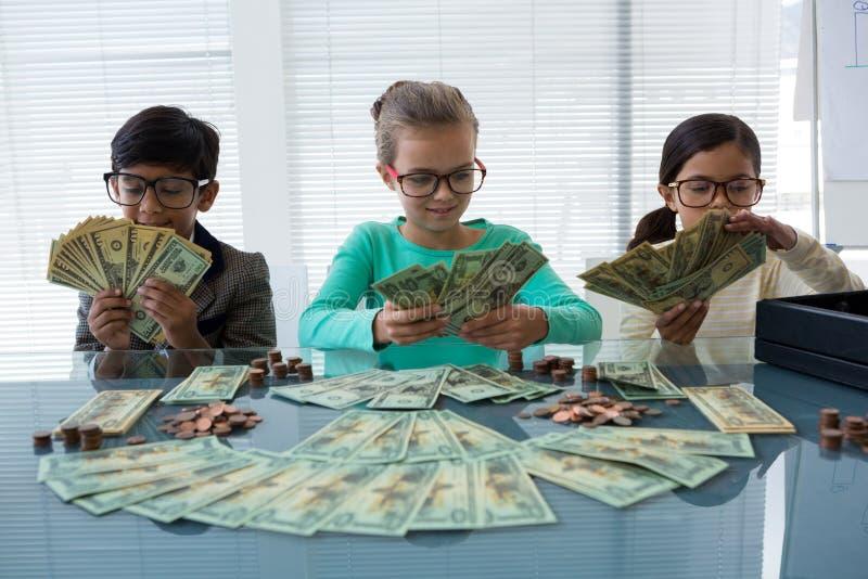 计数金钱的商人在书桌 库存图片