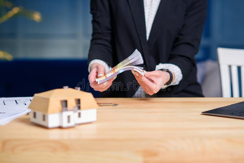 计数金钱的女性不动产房地产经纪商手在买的房子的成功的成交以后 图库摄影