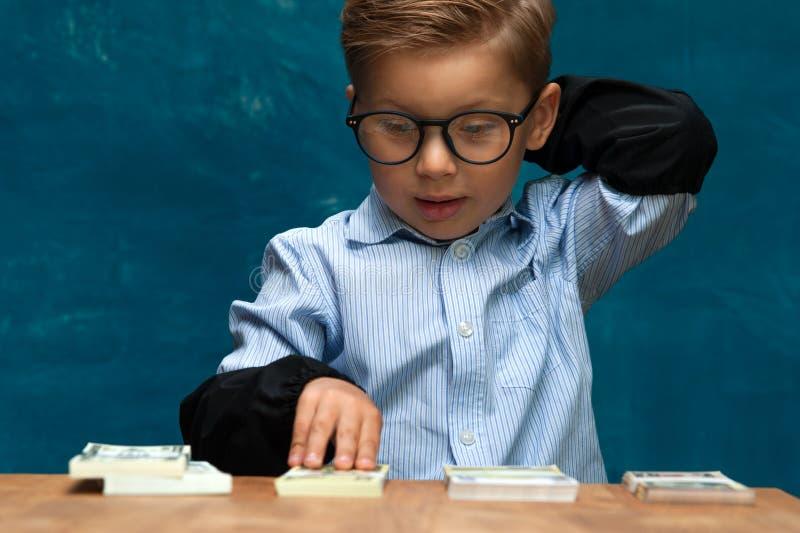 计数金钱的小时髦的男孩在工作场所 免版税库存照片