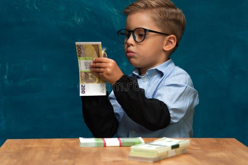 计数金钱的小时髦的男孩在工作场所 免版税库存图片