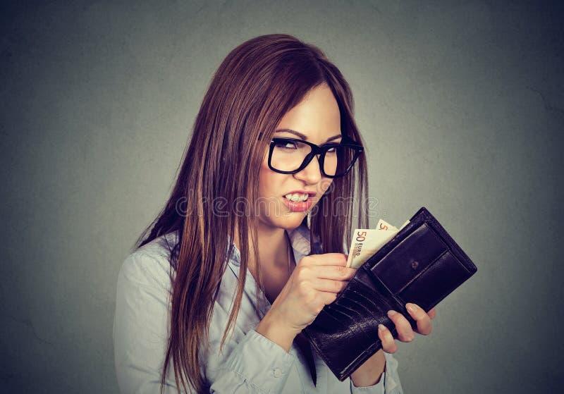计数贪婪的妇女去掉从她的钱包的金钱 免版税库存照片