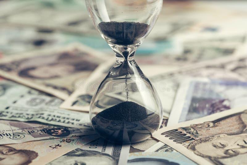 计时与沙子玻璃或小时玻璃在许多国家国际钞票,美元的赛跑或长期投资概念, 免版税库存图片