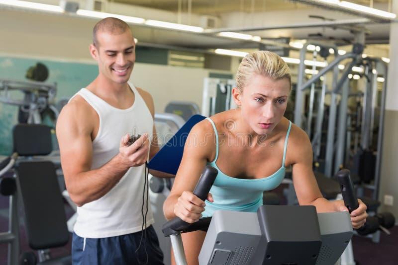 计时他的锻炼脚踏车的教练员客户在健身房 免版税库存照片